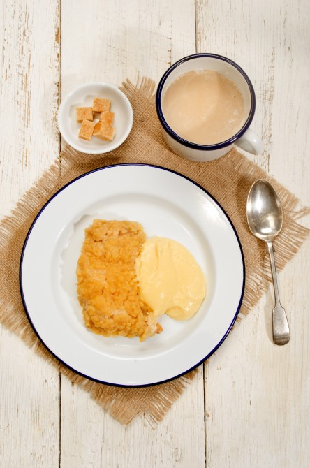 british apple crumble with custard on enamel plate, mug milk coffee and bowl with brown sugar cubes