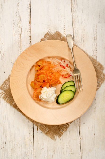 noodle and potato with paprika powder with sour cream and  cucumber slices on wooden plate