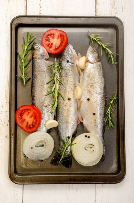 three fresh trout in a roasting tin with tomato slice, garlic, pepper corn, coarse salt and rosemary