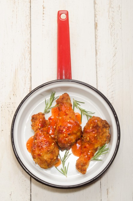 spicy chicken drumstick with rosemary and hot chilly sauce in a pan